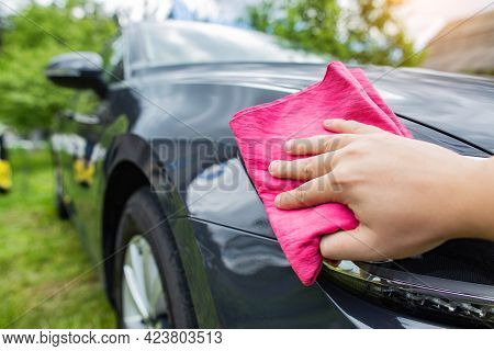 A Hand With A Red Rag Wipes Water Drops On A Car After Washing With Car Shampoo And Wax In The Count