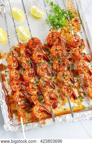Grilled Shrimp Skewers On A Dish Garnished With Cilantro And Lemon Top Down Photo
