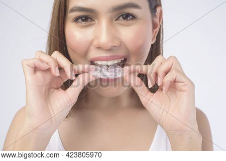 Young Smiling Woman Holding Invisalign Braces Over White Background Studio, Dental Healthcare And Or