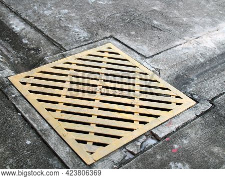 Sewer Manhole Cover In Corner Of Parking Lot Concrete Floor, Close-up Yellow Steel Grating Drain Cov