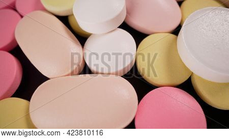 Multi-colored Pills Lie On The Table. The Tablets Are Scattered Onto The Rotating Medical Table. Ana