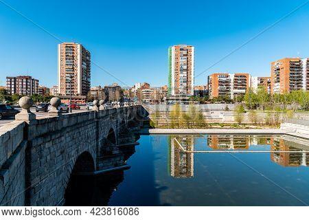Madrid, Spain - March 14, 2021: Madrid Rio. Bridge Of Segovia And Puerta Del Angel Quarter. Reflecti