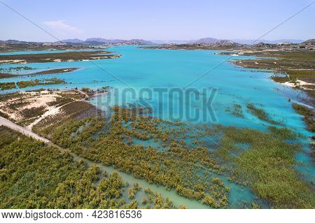 Drone Point Of View Embalse De La Pedrera Reservoir Large Turquoise Colored Lake And Swamp, Sunny Su