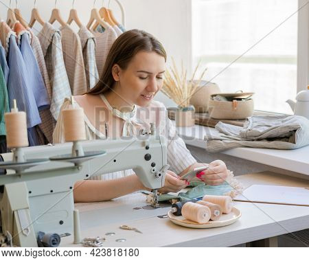 Happy Young Woman Dressmaker Or Seamstress With Cell Phone At Workplace, Checking Online Orders On S