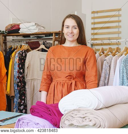 Smiling Woman Fashion Designer Or Atelier Owner Looking At Camera While Standing Near Workplace With