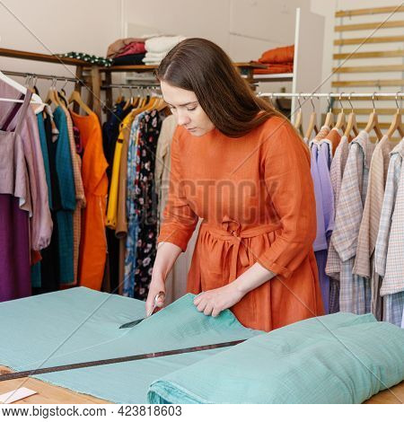 Concentrated Woman Tailor Cutting Fabric On Table, Working On New Clothing At Workplace In Atelier O
