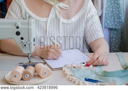 Cropped Shot Of Female Fashion Designer Or Talented Seamstress Drawing Sketch Of New Fashionable Dre