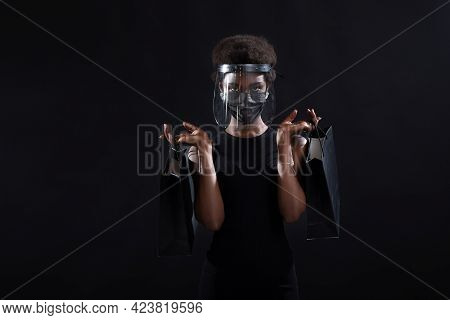 African American Woman In Black Medical Face Mask And Transparent Protective Face Shield Holds Black