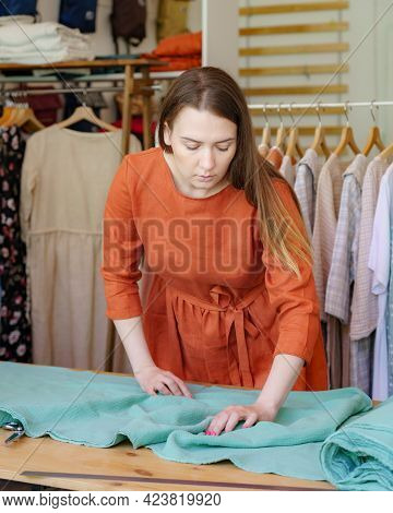 Professional Young Female Fashion Designer At Her Atelier Measuring And Cutting Fabric For Sewing Fa