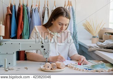 Young Woman Fashion Designer Sitting At Her Workplace With Sewing Machine In Studio And Working On N