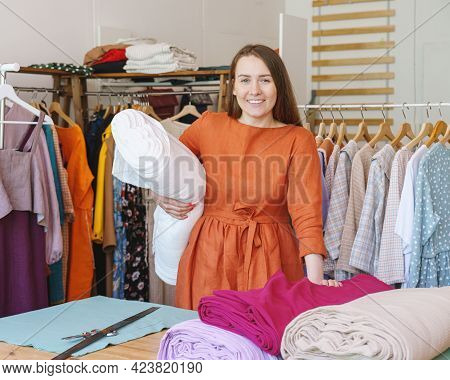 Successful Woman Fashion Designer With Roll Of Fabric For New Collection Smiling At Camera, Creating