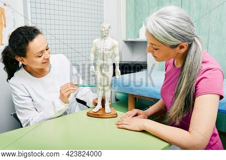 Female Acupuncturist Showing Points On Acupuncture Model Of Human Body To Her Patient At Traditional