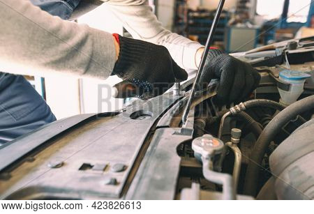 The mechanic fixing the car in the garage