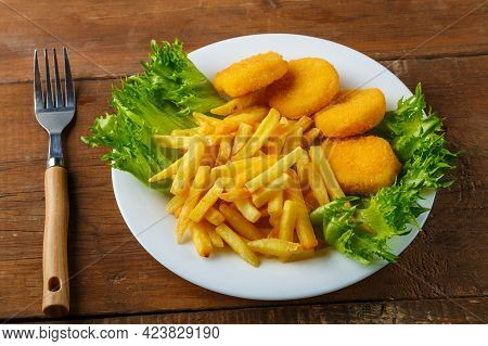 French Fries With Chicken Nuggets In A Plate With Herbs Next To A Wooden Table Next To A Fork. Horiz
