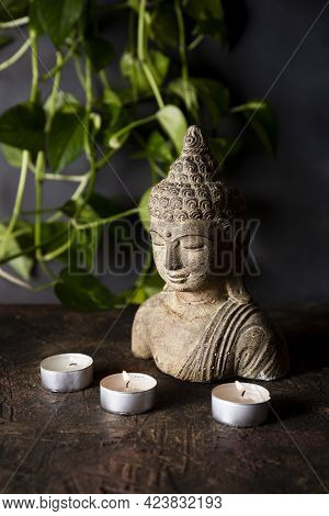 Statuette Of Buddha And Candles On A Dark Background Vertical Photo