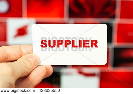 Supplier Is The Word On The Supplier's Business Card. Handing Over A Business Card On A Red Backgrou