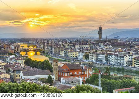 Vivid sunset over river Arno in Florence seen from Michelangelo square. In the picture could be seen Cathedral Santa Maria del Fiore, city hall Palazzo Vecchio and famous bridge Ponte Vecchio