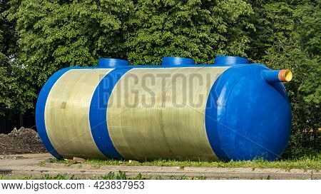 A Huge Blue Container For Collecting Sewage Waste Lies On The Grass