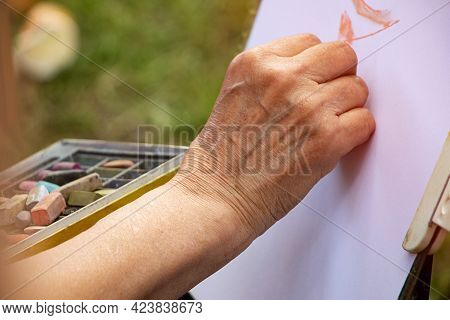 Street Artist Holding A Box With Multicolored Crayons And Pencils For Drawing.close Up Photography O