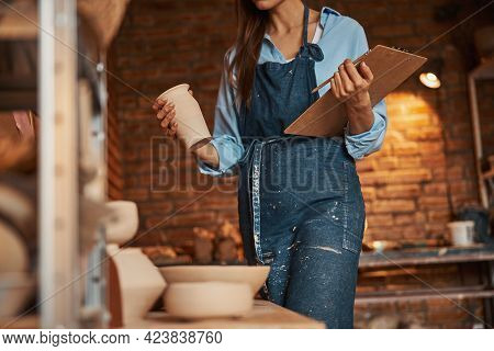 Young Cheerful Craft Woman With Clipboard In Hands Standing In Art Studio
