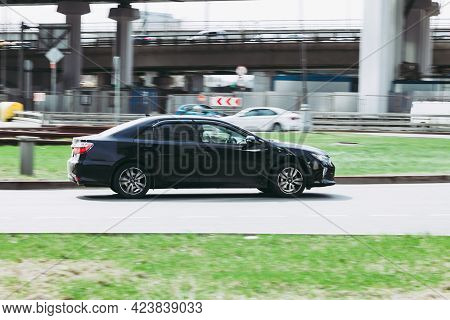 Moscow, Russia - April 2021: Toyota Camry Xv50 Rolling Shot Down The Street On High Speed. Black Shi