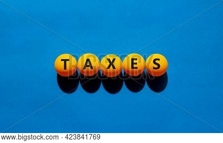 Taxes Symbol. Orange Table Tennis Balls With The Words 'taxes'. Beautiful Blue Background, Copy Spac