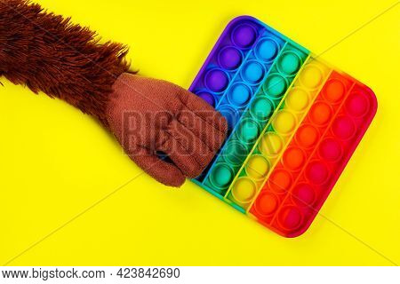 Pop It Fidget Toy. Fashionable Anti-stress Gift On A Yellow Background. Lgbt Flag And Rainbow Colors