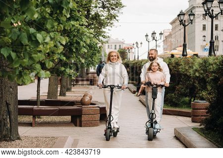 A Family In White Clothes Rides Electric Scooters In The City.outdoor Activities