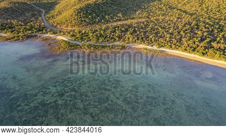 Drone Aerial Over The Ocean At Low Tide Showing Underwater Detail And Coastal Vegetation In The Warm
