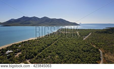 Aerial View Over A Bushland Beachfront Settlement With A Long Stretch Of Sandy Beach And Mountain Is
