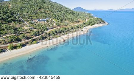 Aerial View Over Coastline And Clear Blue Sea Towards Bushland Shore With House Cape Gloucester Aust
