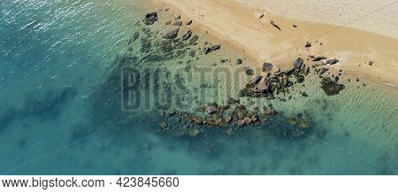 Rocks On The Shoreline And Underwater In A Sparkling Blue Ocean At Low Tide On A Tropical Sandy Beac