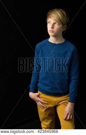 Portrait Of Stylish Teenage Boy. Handsome Teenager Wearing Blue Pullover And Yellow Pants Posing Aga