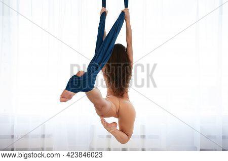 A Girl Does Exercises In An Air Hammock, An Air Yoga Hall With An Air Hammock, A Girl Training In A