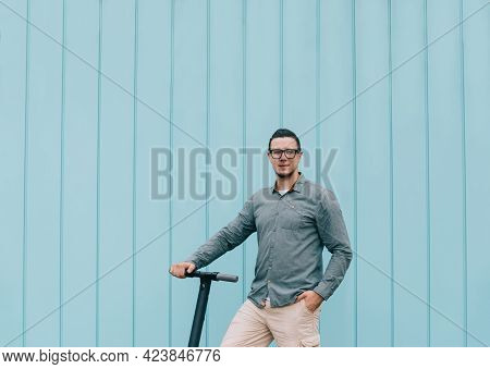 Man In Shirt Standing With E-scooter In Street.