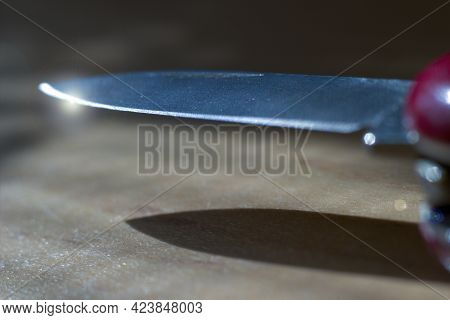 Extreme Focus Of Pointy Sharp Knife With Light Flare At The Edge. Shiny Metal Object Against Wooden