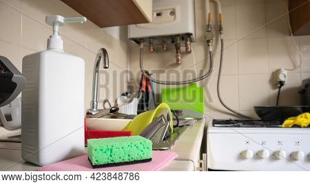 Green Sponge And Liquid Soap Dispenser For Washing Dishes On A Dirty Sink Completely With Dishes And