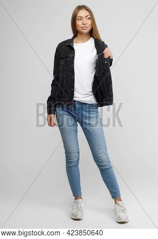 Girl In A Denim Black Jacket And Blue Denim Pants On A White Background