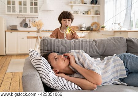 Sleepy Young Mom Awake With Bored Small Kid Making Noises. Tired Mommy Lying On Sofa Annoyed Try To