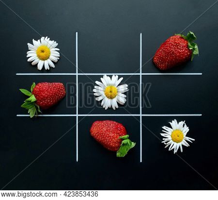 Tic Tac Toe On A Black Background Made Of Chamomile Flowers And Strawberries.  Flat Lay.  Natural Co