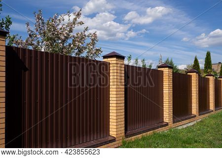 A Browna Brown Metal Fence With Brick Posts Against A Blue Sky. A High Wall Encloses The Private Are