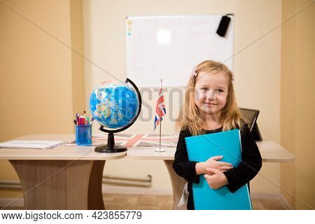 Portrait Of Diligent Girl Looking At Camera In The Classroom.