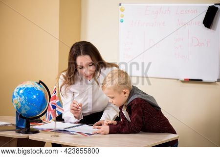 Teacher Helping Male Pupil With Reading At Desk.