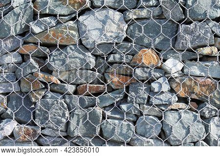 Closeup Of A Gabion Dam Surface As A Background. Stones Of Different Shapes And Sizes In Wire Mesh S