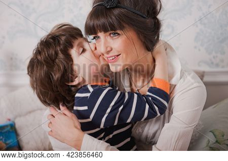 Boy Kisses His Mom And Hugs. Happy Young Woman Have Fun With Cute Child Baby Boy. Mom And Son Sit On