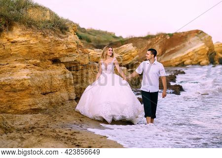 A Beautiful Bride And Groom Walk Along The Sandy Rocks Along The Sea. Handsome Groom Holds The Hand