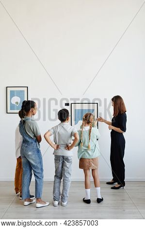 Vertical Back View At Diverse Group Of Children Listening To Female Tour Guide While Visiting Modern