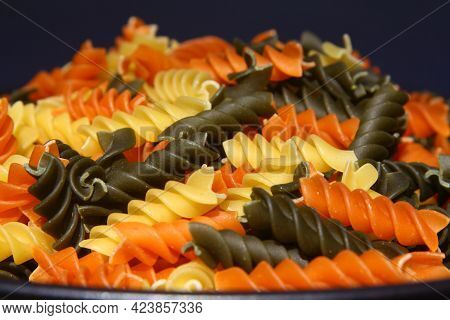 Three Colors Rotini Pasta. Pasta Fusilli Tricolore Background. Abstract Texture Of Colorful Pasta. P