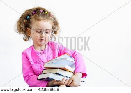 Serious, Brooding, Cute Smart Little Girl In Funny Big Glasses Reading A Stack Of Paper Books. Train