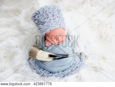 Portrait of newborn baby boy swaddled in light blue fabric and wearing furry caucasian hat sleeping in studio. Adorable infant child napping with traditional horn